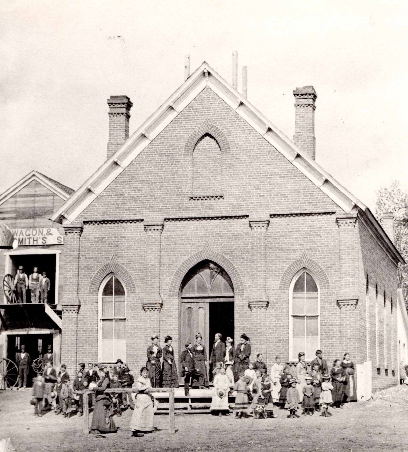 group of people standing in front of church building