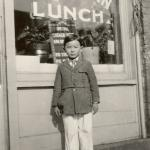 Immigrant Boy Standing in Front of a Local Business